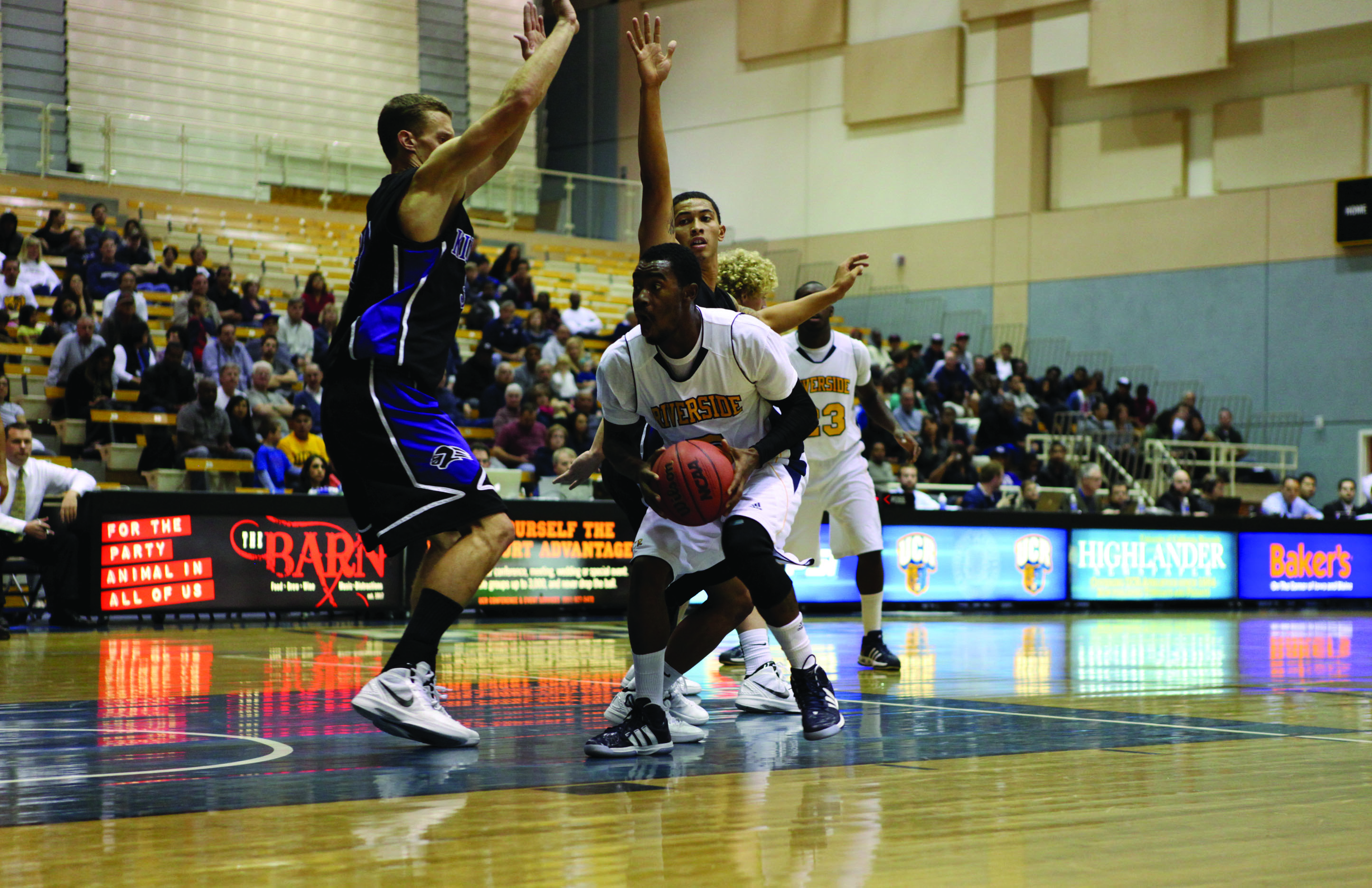 Guard Kareem Nitoto drives to the basket past a duo of Cal Lutheran defenders.