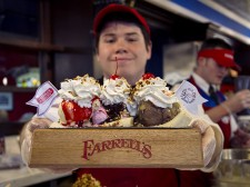 Farrell's employee Donovan proudly presents one of their most famous sundaes, The Pig's Trough. Courtesy of Leena Butt
