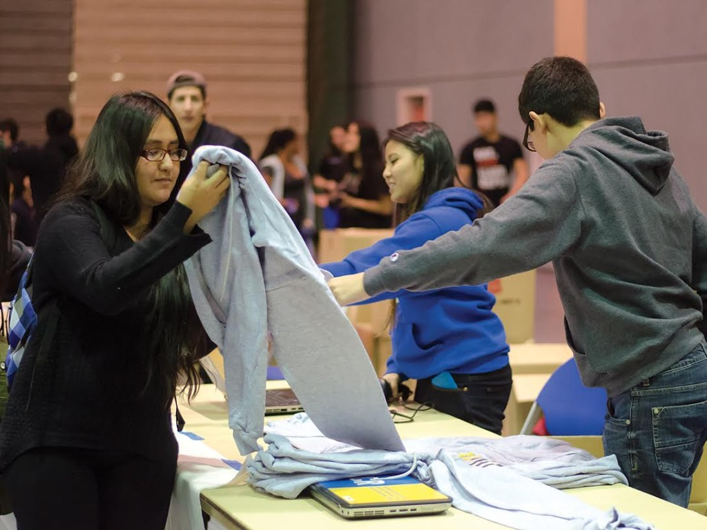 ASPB volunteers hand out sweaters to students after checking their ID.
