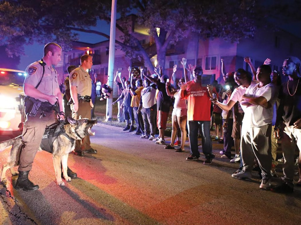 Police officers stand to confront a crowd they're trying to break up a on Canfield Dr. in Ferguson on Saturday, Aug. 9, 2014. Earlier in the day police had shot and killed an 18 year-old man on the street and the crowd of people were upset.Photo By David Carson, dcarson@post-dispatch.com