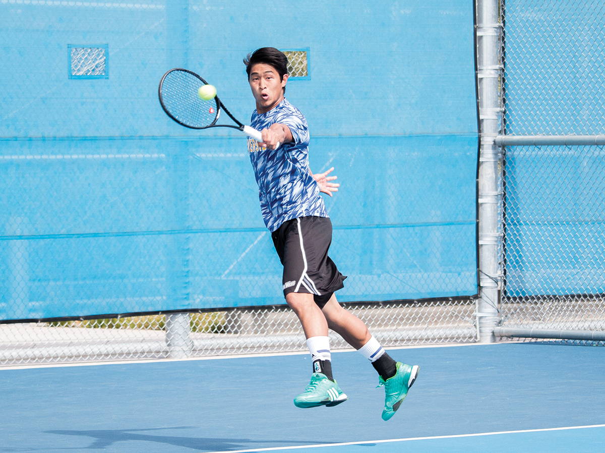 Sean Yun reaches to hit the ball over the net.