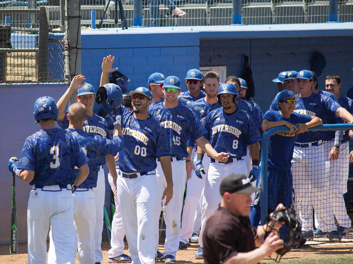 The UCR men's baseball team goes out to congratulate Ellis on making it safely back home.