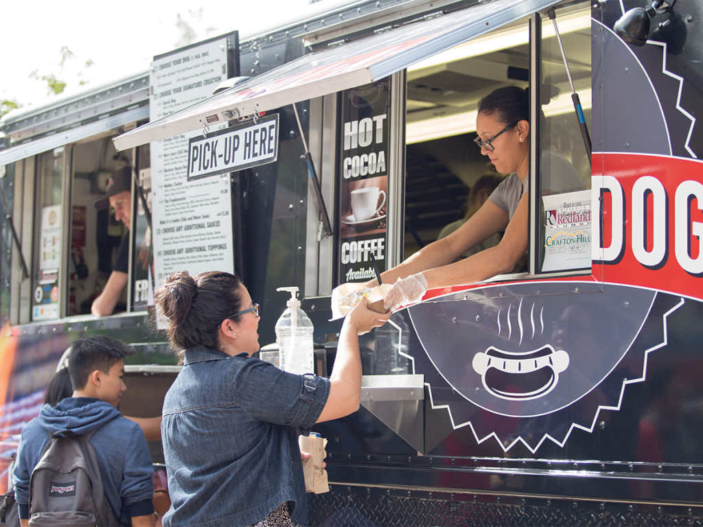 A student picks up her lunch from Grill-A-Dog food truck.