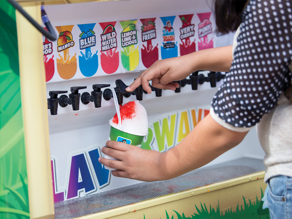 A student customizes her shaved ice at the Kona Ice food truck.