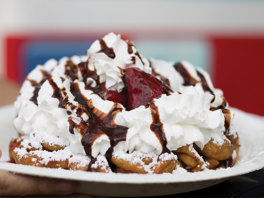 A funnel cake with whipped cream, strawberries, and chocolate drizzle from The Sweet Stop.